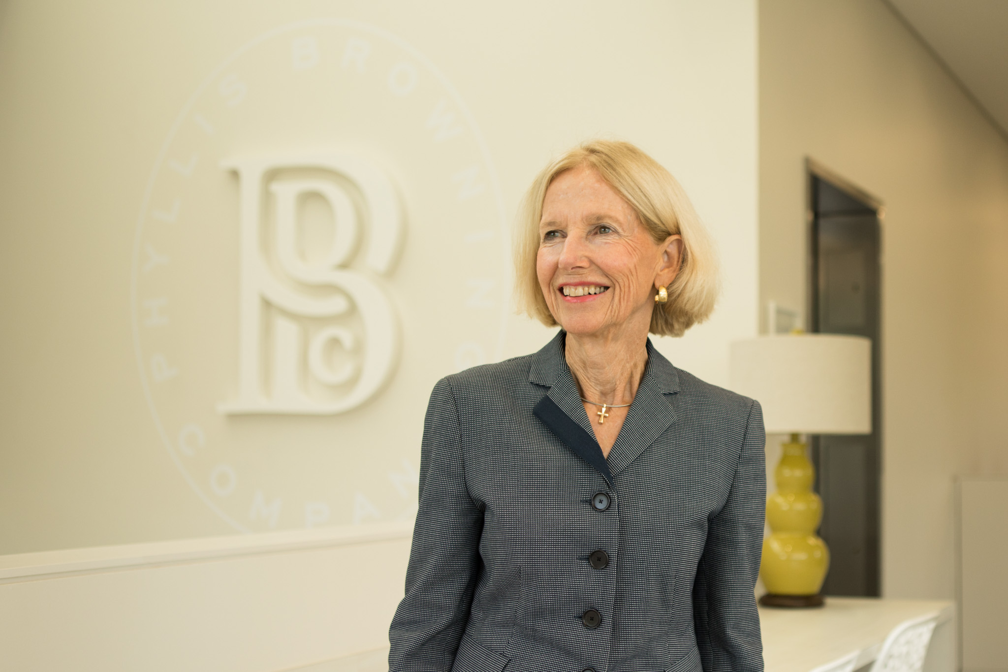 Phyllis Browning Company CEO Phyllis Browning stands near the large company logo on the wall.