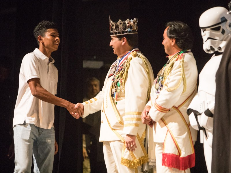 Scholarship recipient Marcel Buie shakes the hand of El Rey Feo LXIX Fred Reyes and his royal court at the Rey Feo Scholarship Awards Ceremony.