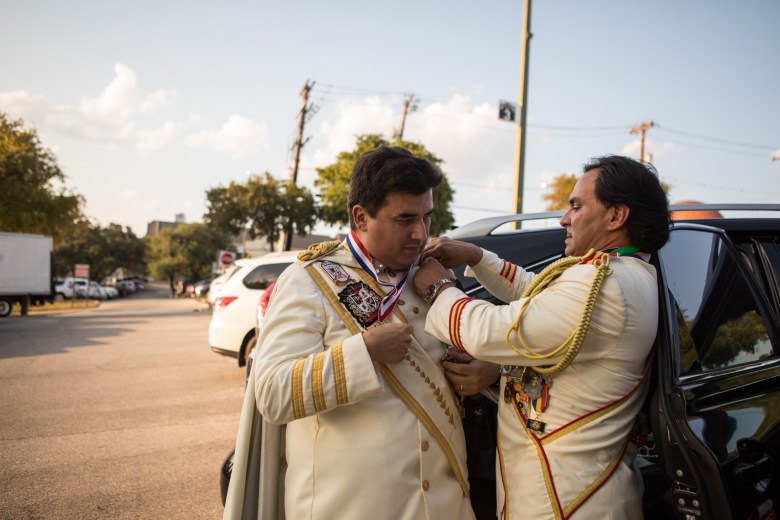 Augie Cortez (left) fixes the Fiesta medals on El Rey Feo LXIX Fred Reyes for the Rey Feo Scholarship Awards Ceremony.