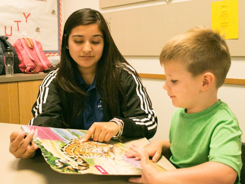 YMCA Site Director Autumn Molina helps Austin, 4, read a book at the YMCA After School Care Program at the Sunshine Cottage School for Deaf Children.