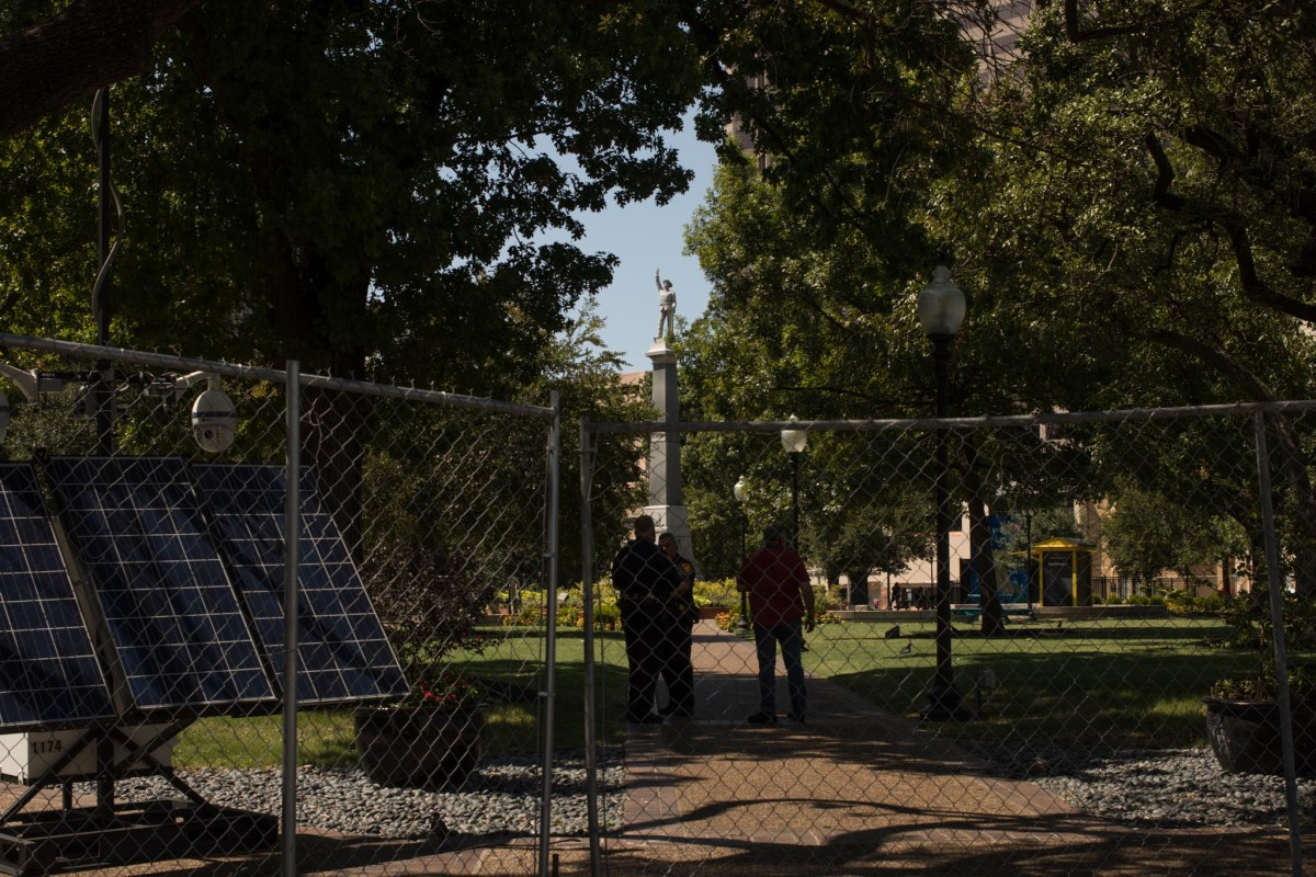 A fence was erected around Travis Park. The Confederate monument in the center will soon be removed.