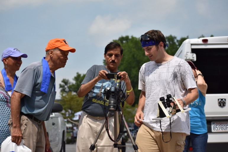 Dan Abramov (right) lets Eclipse Day attendees take photos of his photo of the total solar eclipse.
