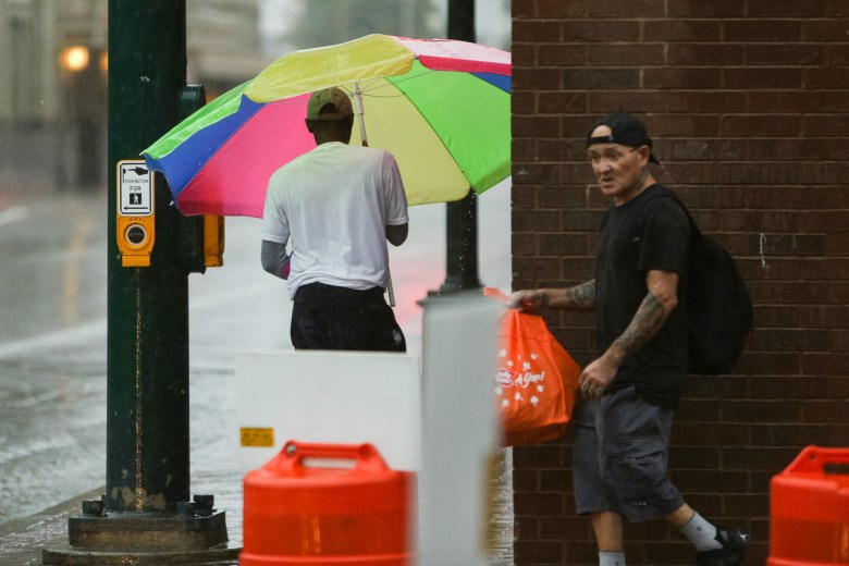 A large beach umbrella is used to shield a pedestrian from heavy rains downtown San Antonio.