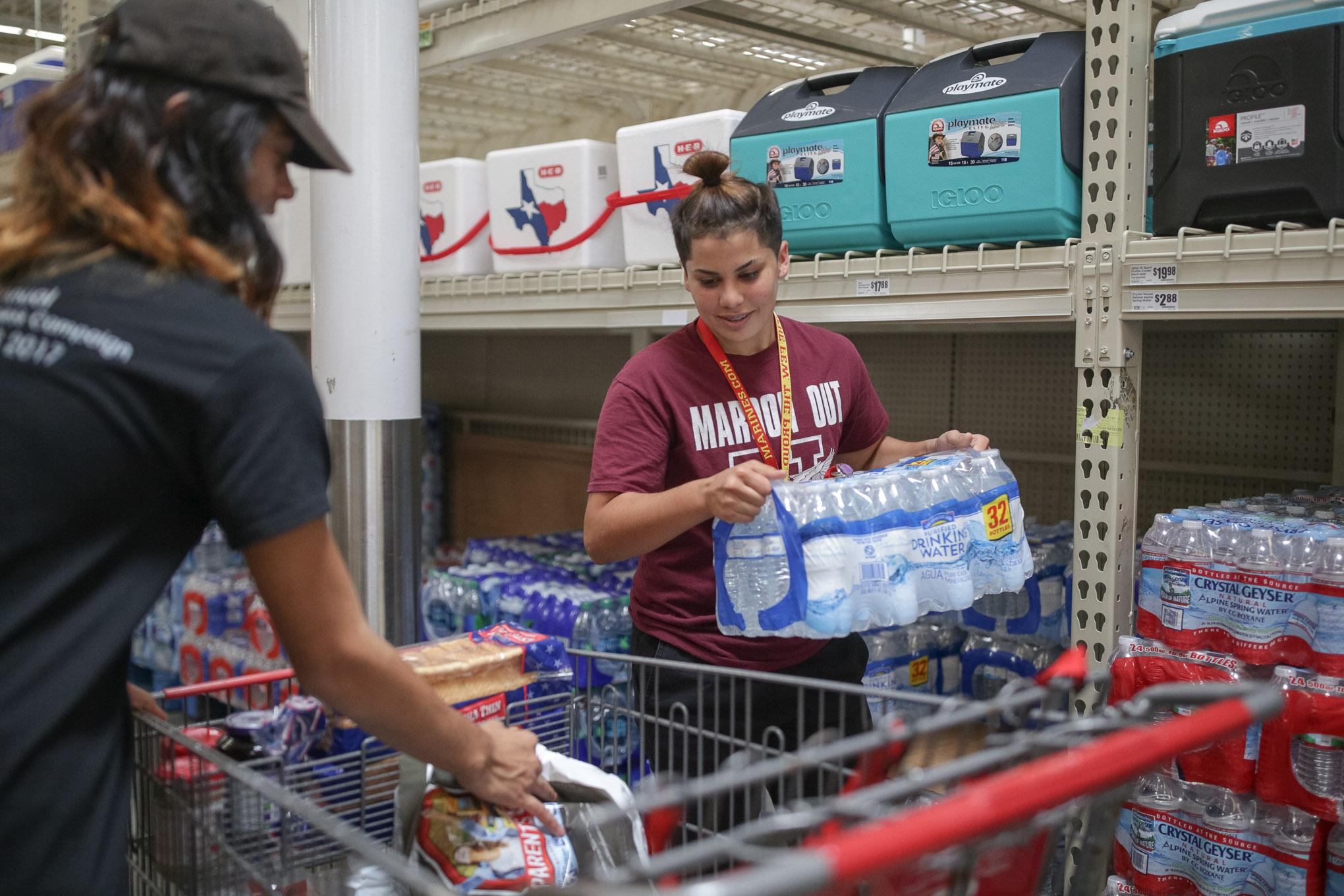 Joshua De La Cruz and Amanda Herrera stock up on cases of water in preparation for the weekend's weather.