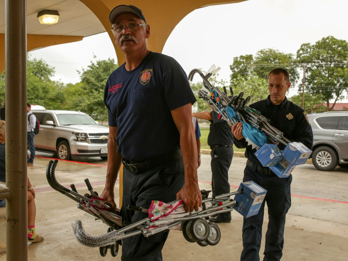 Members of San Antonio Fire Department arrive with strollers for evacuated families from the Texas coast.