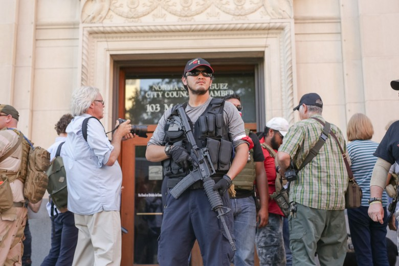 Members of TITFF (This is Texas Freedom Force) secure Brandon Burkhart in front of the Municipal Plaza Building.