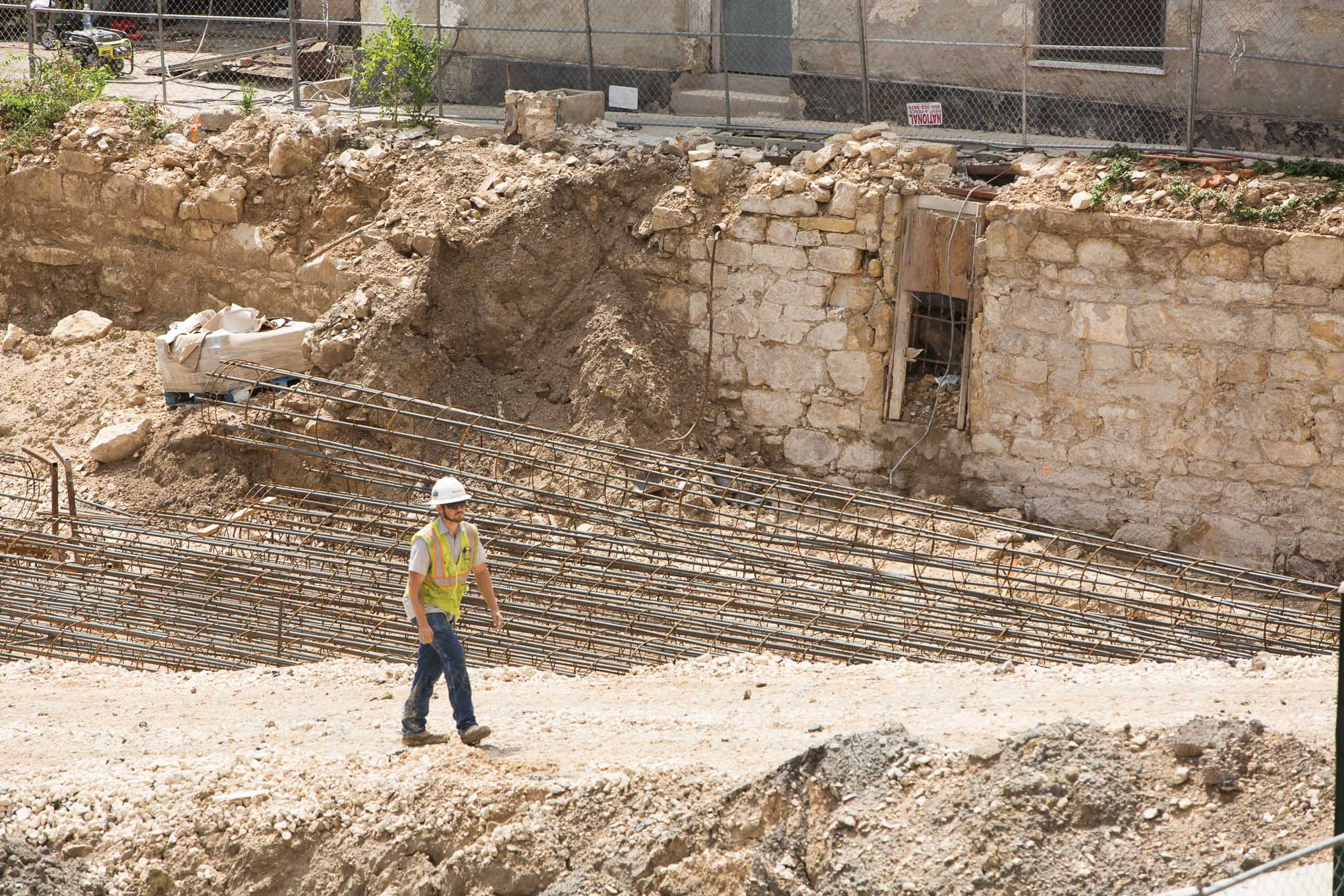 Construction crews work on the development project alongside historic wall structures where the Solo Serve building once stood.