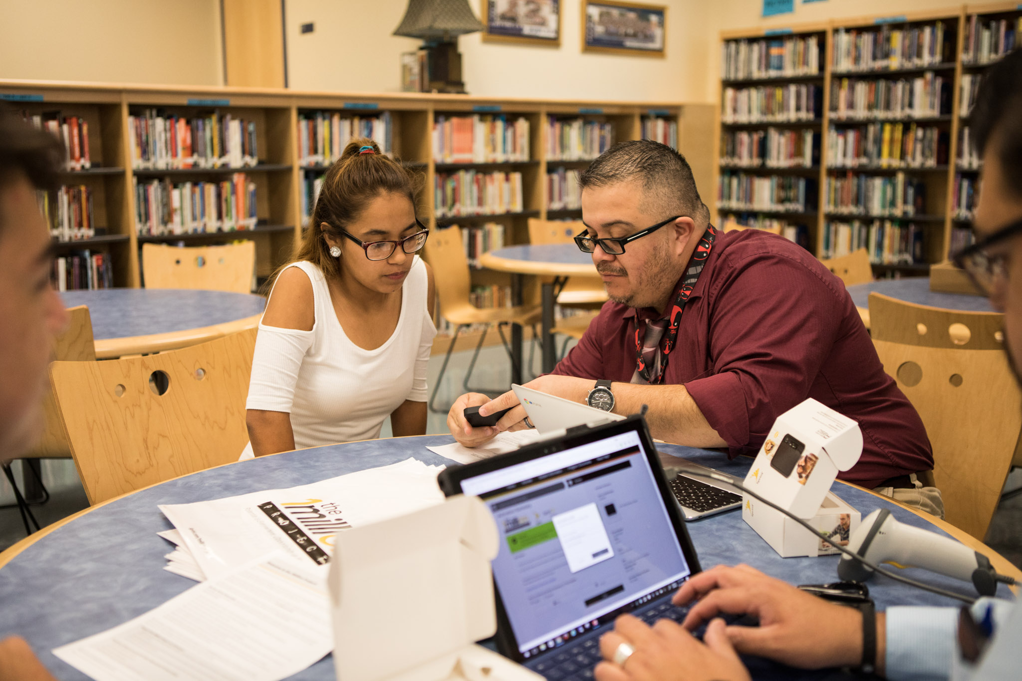 SSAISD Technology Support Specialist Mike Ortiz Jr. explains how to use the personal hotspot to Ariana Livar.
