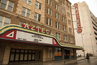 A police officer rides his bike past the front of the Aztec Theatre.