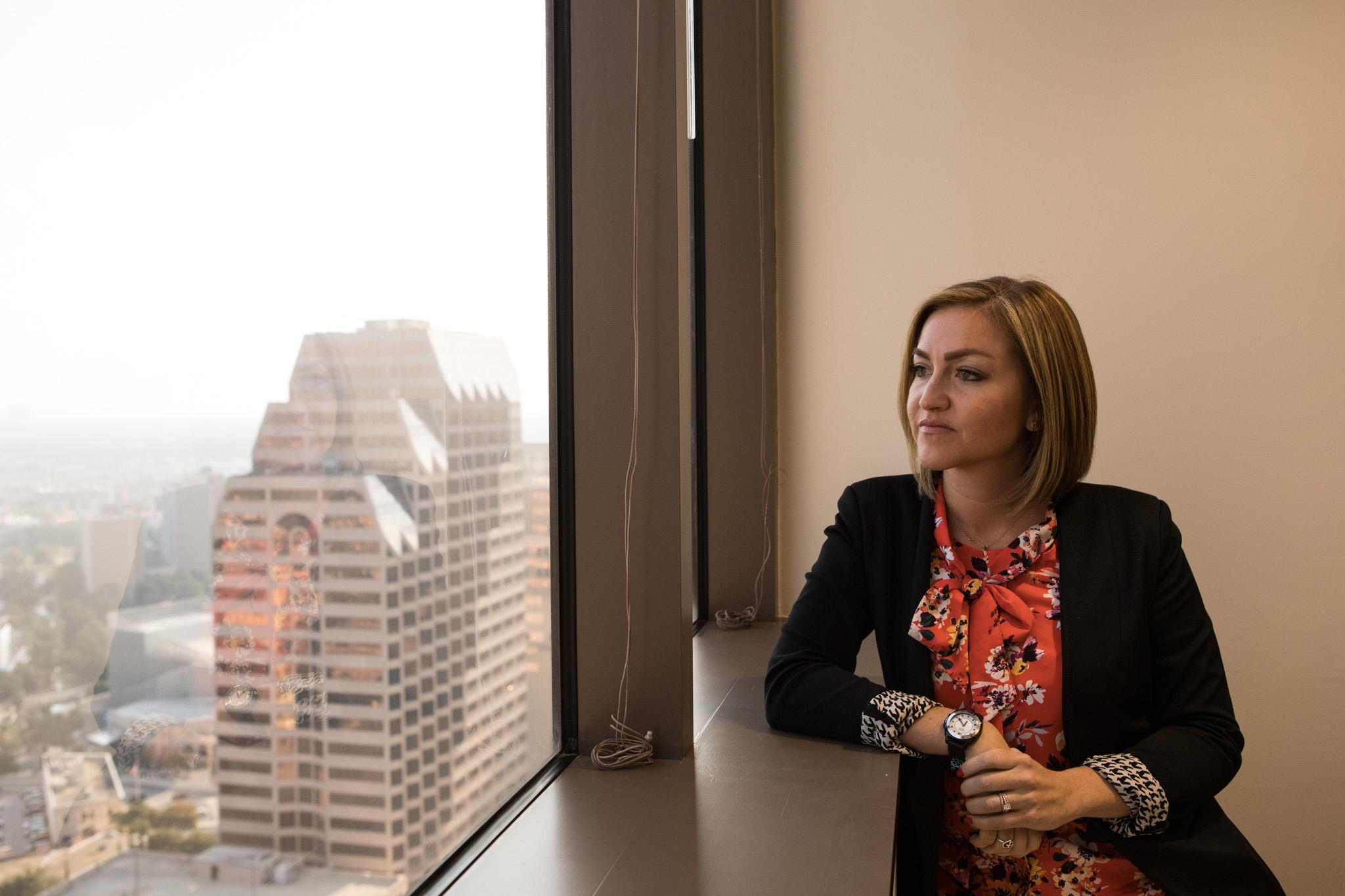 San Antonio EDF President & CEO Jenna Saucedo-Herrera looks out the window of the new San Antonio Economic Development Foundation in the Weston Centre.