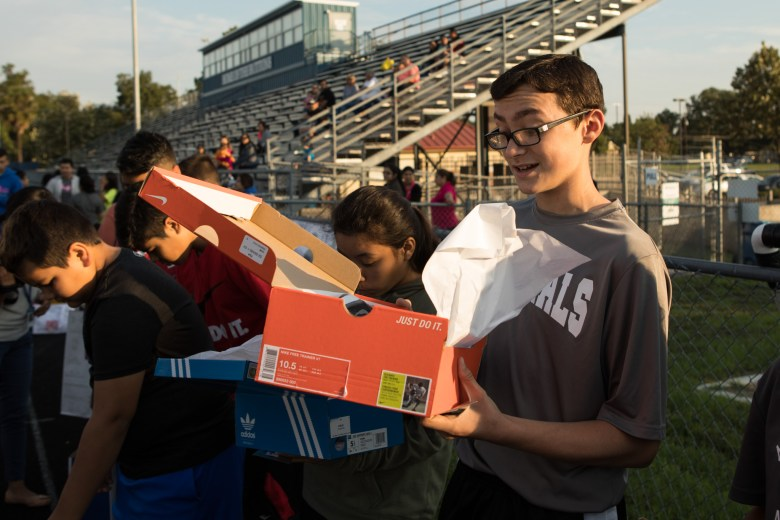 Madden Lanoue, 13, opens up his free shoes from Champs at the Forward in Fitness program kickoff at Central Catholic High School.