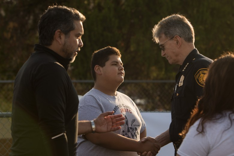 Andres Gonzalez, 14, (center) introduces himself to San Antonio Police Chief William McManus (right) and Councilman Roberto Treviño (D1) (left) at the Forward in Fitness program kickoff at Central Catholic High School.