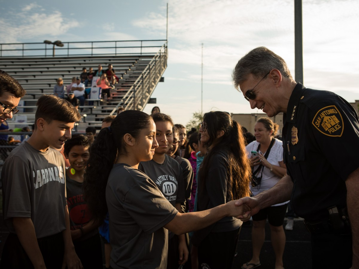 San Antonio Police Chief William McManus shakes the hand of Laura Martinez at the Forward in Fitness program kickoff at Central Catholic High School.