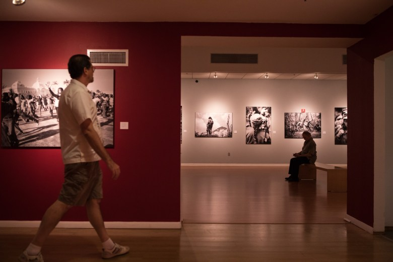 People walk through the Mexican Cultural Institute San Antonio to view the images in the show Pedro Valtierra: Imágenes en Conflicto.