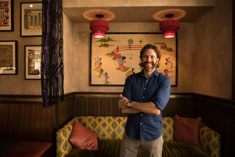 Owner Steve Mahoney stands next to the Japanese-inspired decor of Hanzo.