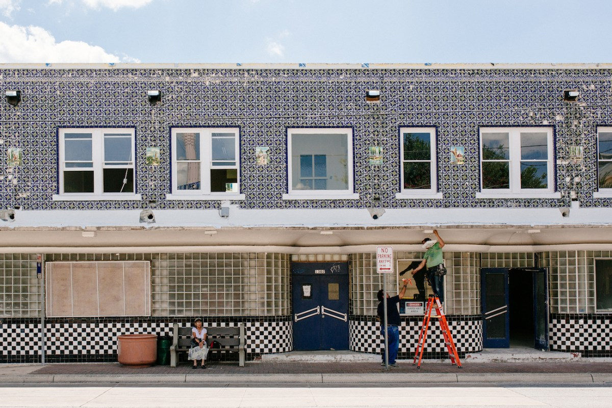 Workers fix up an old building across the street from the Guadalupe Theater.