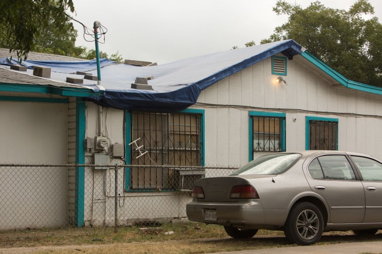Tarps cover the roofs of houses in need of repairs.