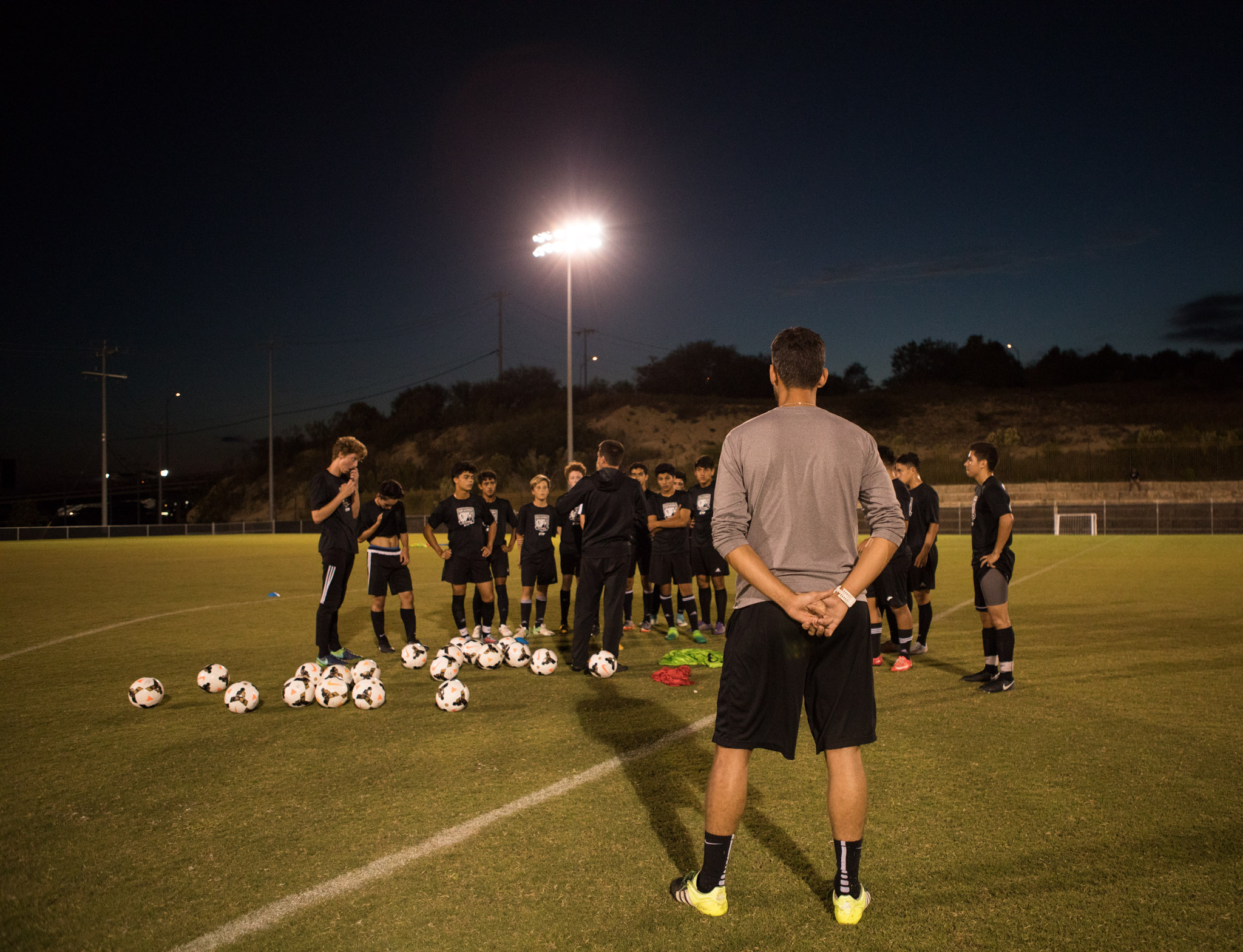 San Antonio FC's Ryan Roushandel stands near the SAFC Pro Academy team he coaches at S.T.A.R. Soccer Complex.