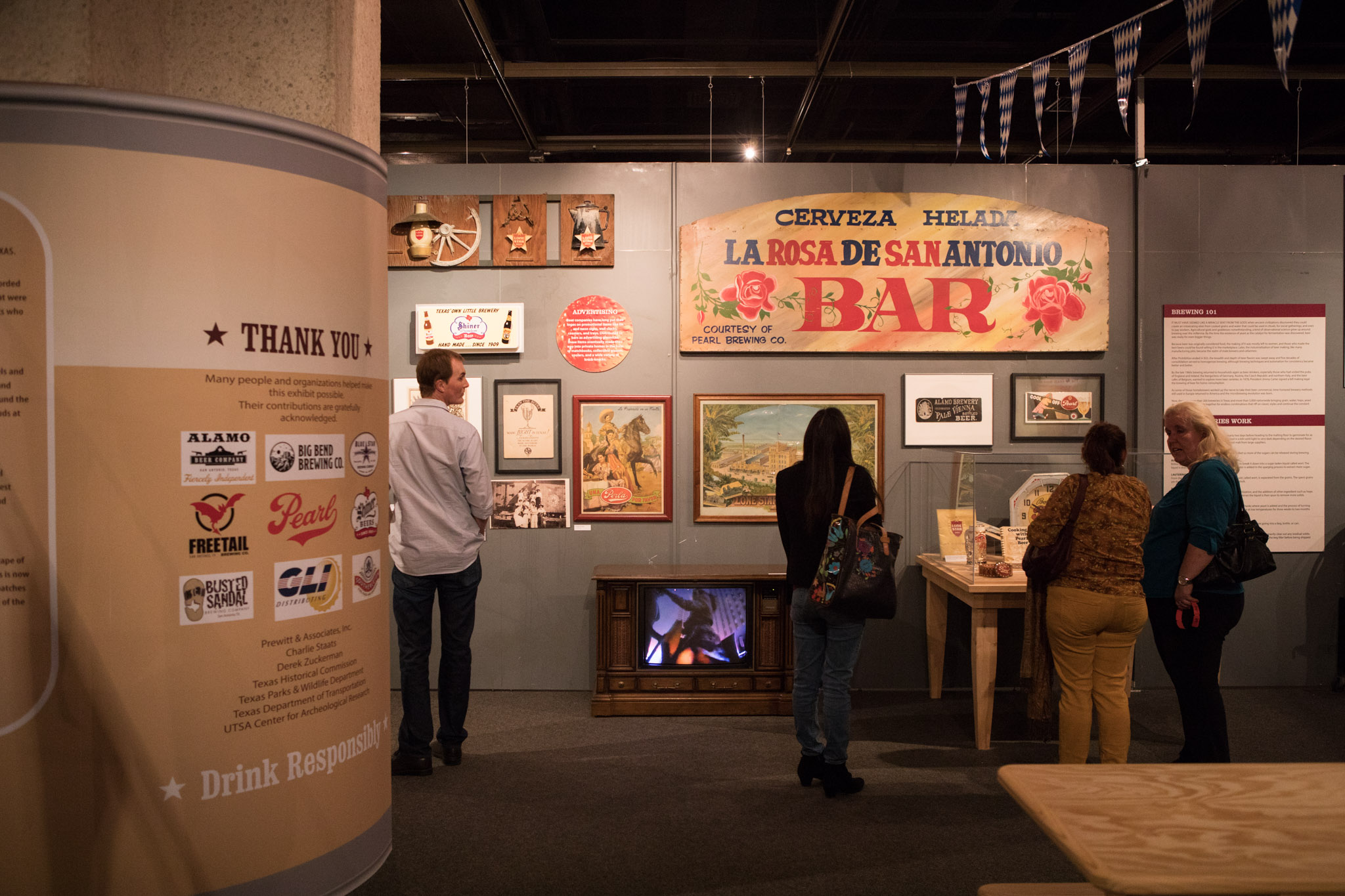 """Vintage brewery signs line the walls at the UTSA Institute of Texan Cultures """"Brewing Up Texas"""" exhibit."""