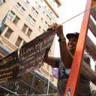 Walter Koch hangs up haikus written in chalk along Houston Street during Chalk It Up.