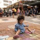 Isabella, 1, draws on the sidewalk on Houston Street during Chalk It Up.