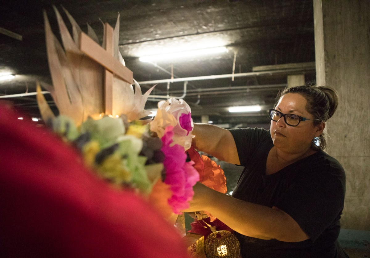 Ana Fernandez attaches flowers to the Floating Day of the Dead Altar for Día De Los Muertos.