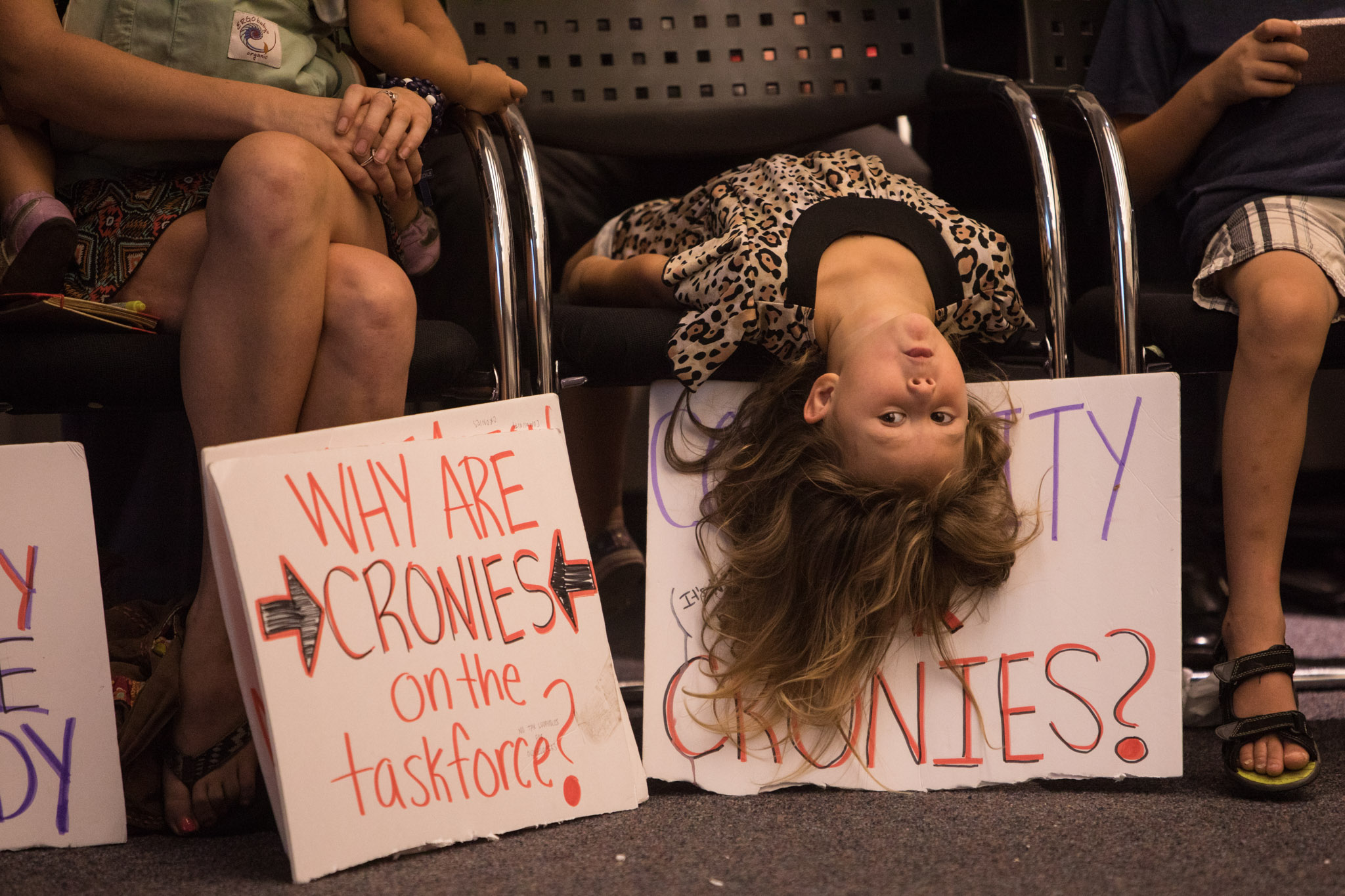 A young girl wiggles around with signs before the first Mayor's Housing Policy Task Force meeting at San Antonio Central Library.