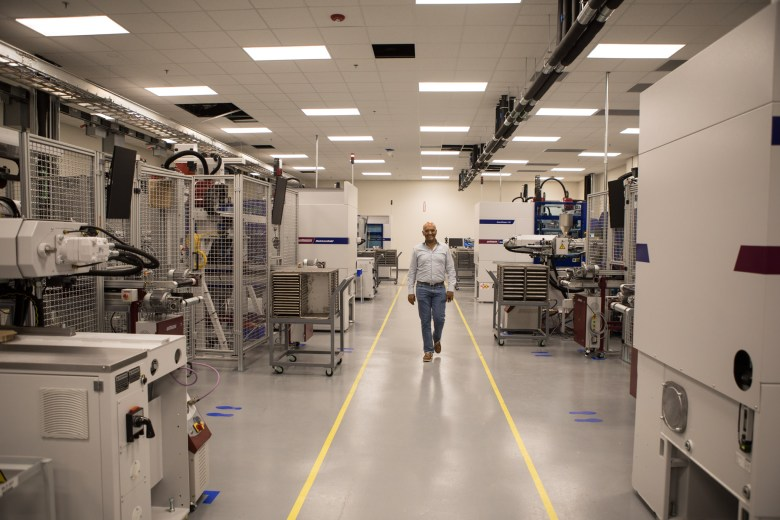 Indo-MIM CEO Krishna Chivukula Jr. walks past the injection molding machines in the new Indo-MIM factory at Port San Antonio.