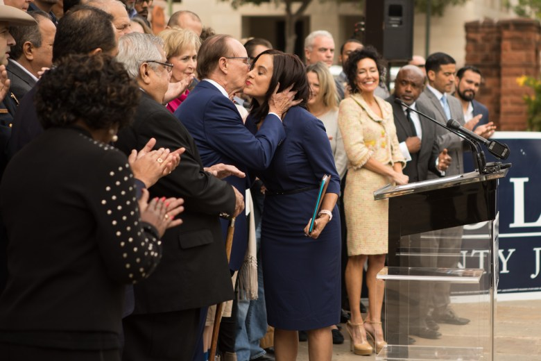 (From left) Bexar County Judge Nelson Wolff kisses _______ on the cheek at his campaign announcement in front of Bexar County Courthouse.