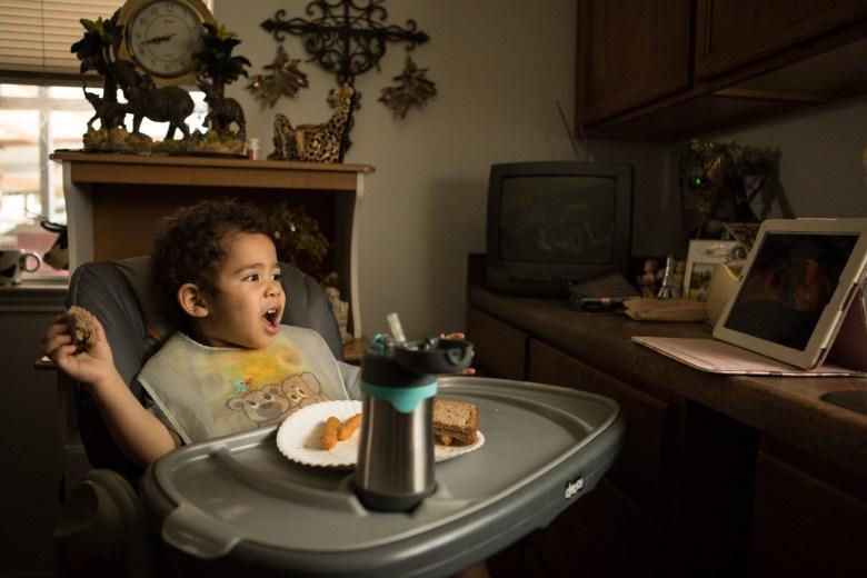 Sekai Jose Mercado, 2, eats a sandwich as he watches a movie in the kitchen.