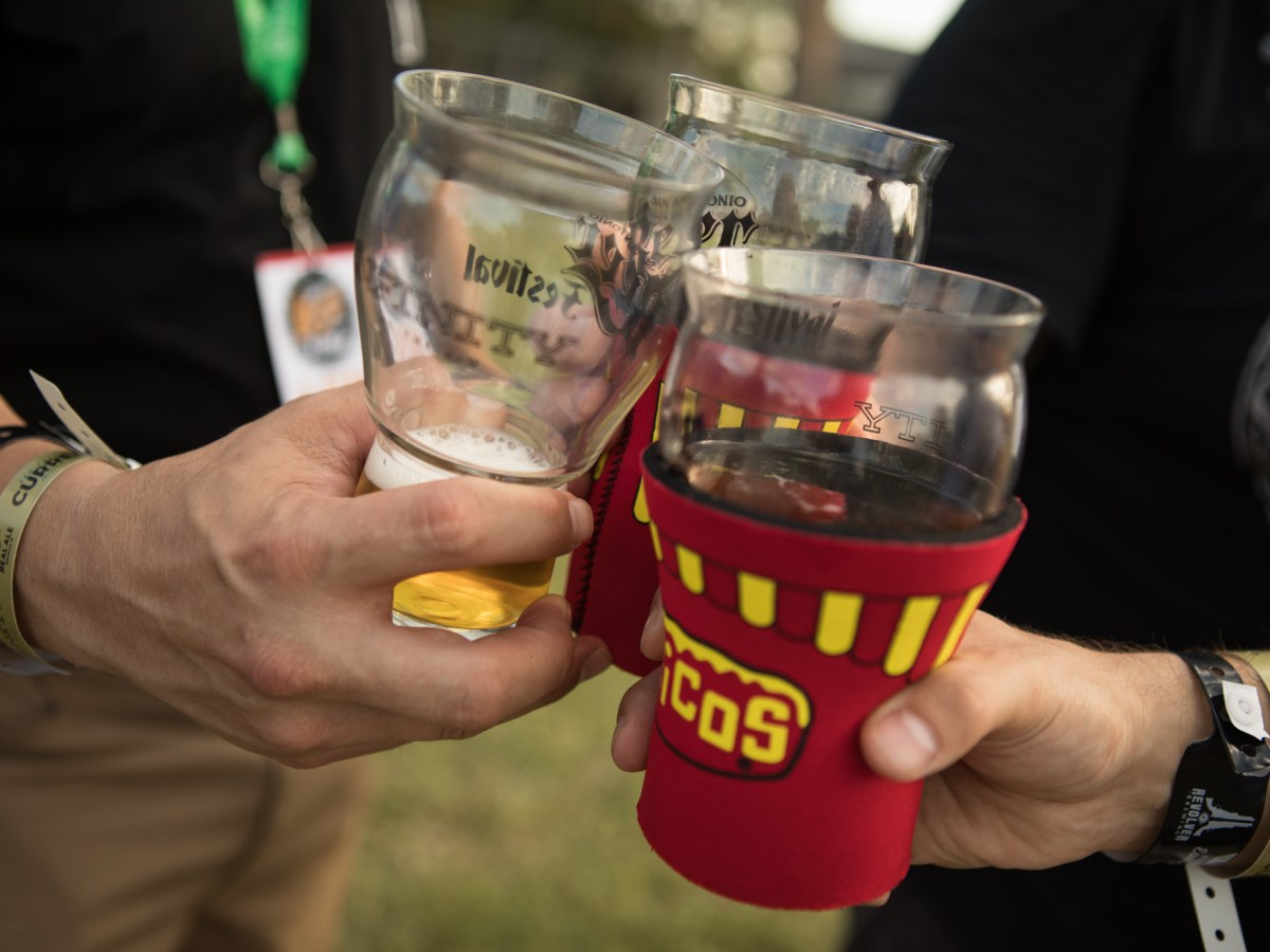 Three men clink their glasses in celebration at the San Antonio Beer Festival.
