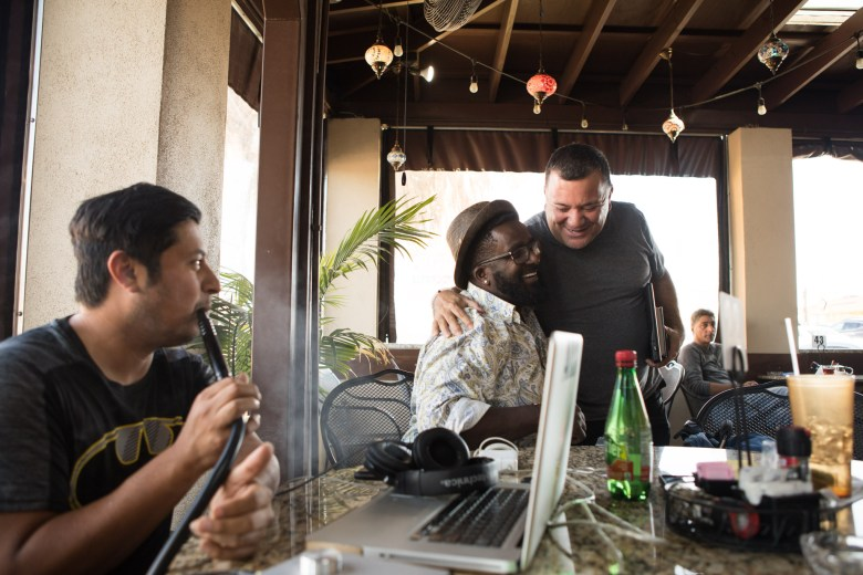 (From left) David Davila and Wallace Pope greet a friend at Naara Cafe, where they smoke hookah daily.