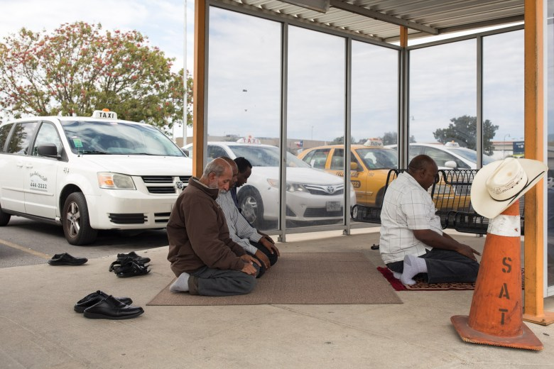 Ahmad Mahood (center) kneels with fellow taxi cab drivers during a moment of prayer.