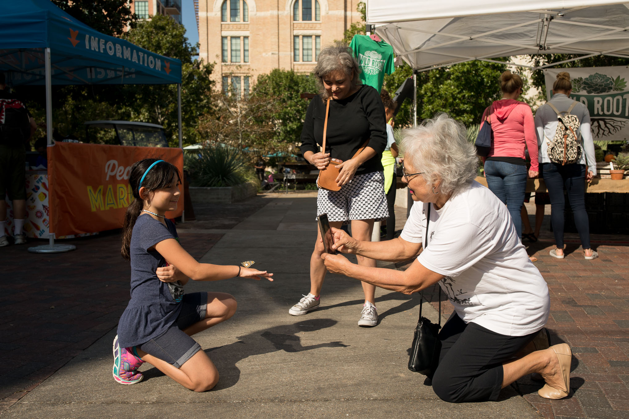 Sophia Gonzales, 8, holds out a monarch butterfly as her grandmother Erlinda Cortez takes a photograph.