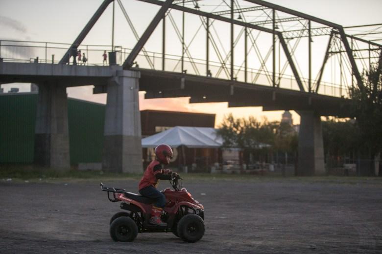 A boy rides his toy tractor near the Hays Street Bridge.