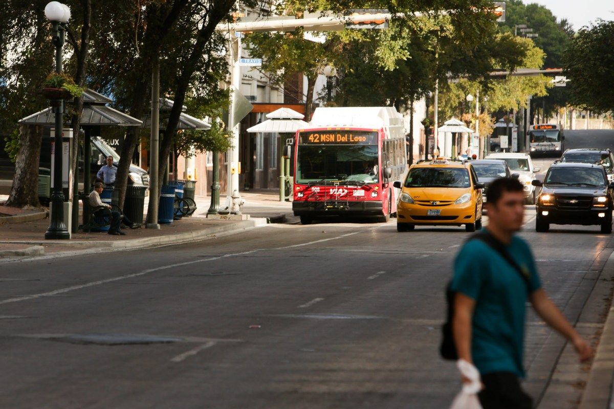 Busses, taxis, and pedestrian vehicles travel South on Saint Mary's Street.
