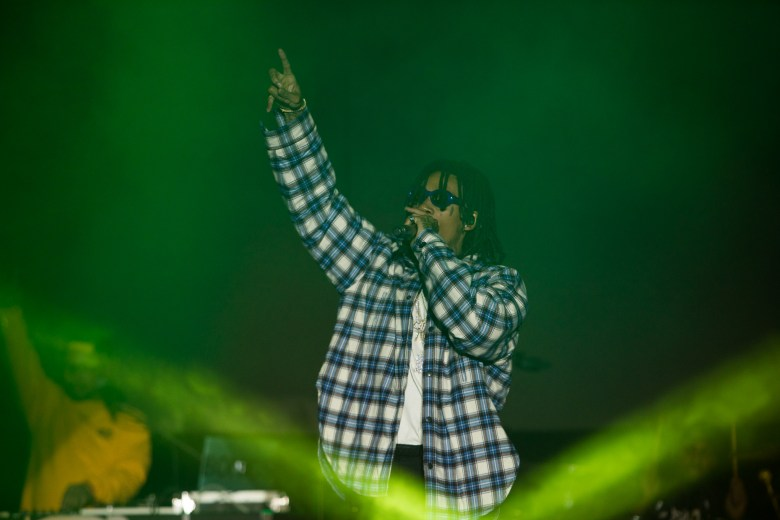 Wiz Khalifa points to the sky during a performance.