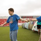 Asa Hart (center) grabs the hands of his sister Aimee Brown (not pictured, left) and his mother Carole Trisler (right) to dance to the music next to the construction of the world's largest blanket fort for autism awareness.