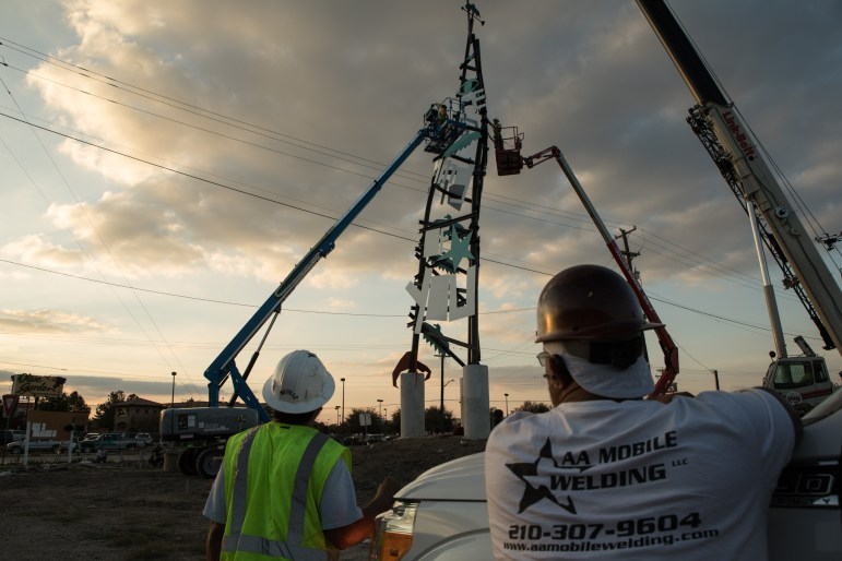 Construction workers watch as the last section of the Dream Song Tower is placed on the top of the structure.