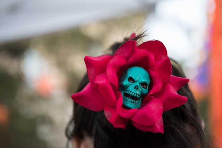 A face painter for HippysFX wears a flower with a skull in her hair in honor of Día de los Muertos at the Pearl.