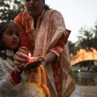 A young girl prepares to place her candle in the San Antonio River during the Diya Ceremony at Diwali San Antonio: Festival of Lights.