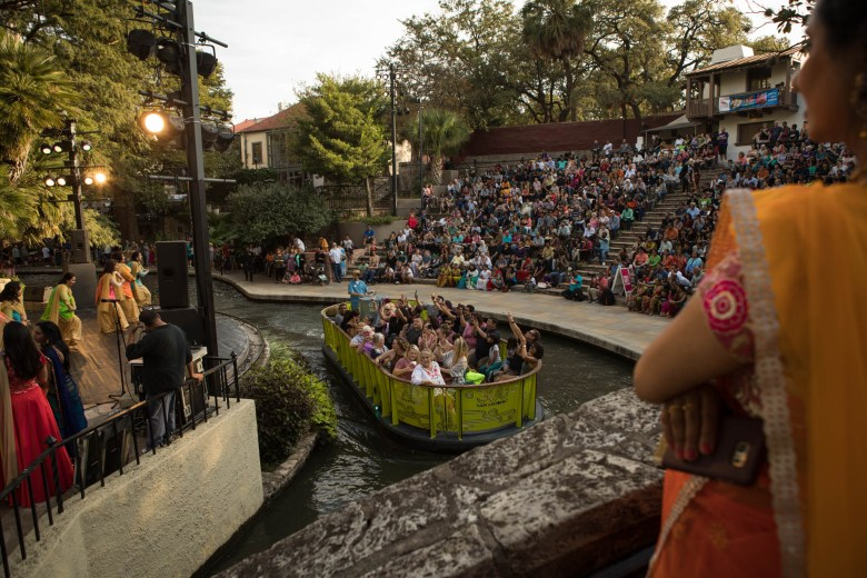A new San Antonio River Barge passes the dance performances at Arneson River Theatre during Diwali San Antonio: Festival of Lights.