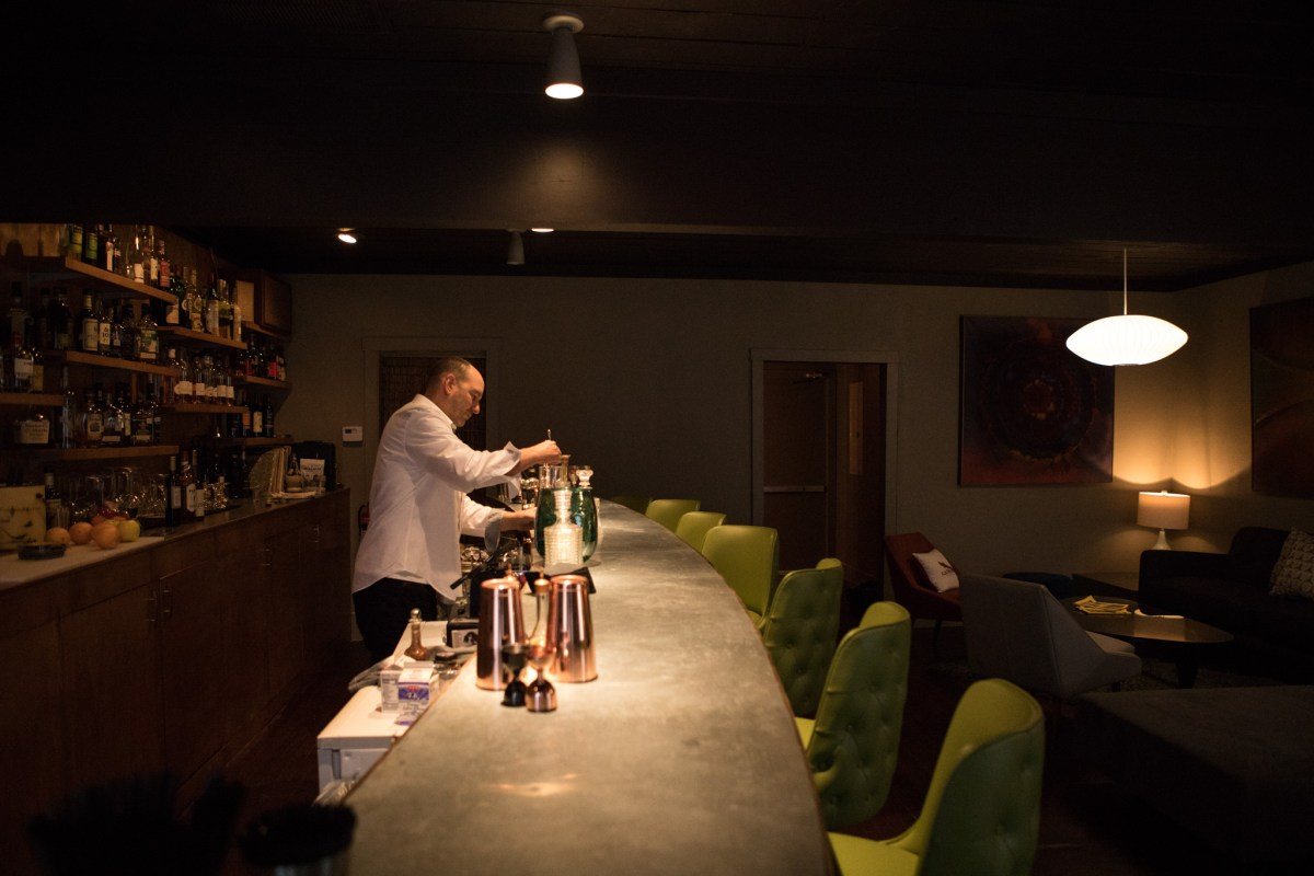 Olaf Harmel prepares the bar at The Modernist before opening for the evening.