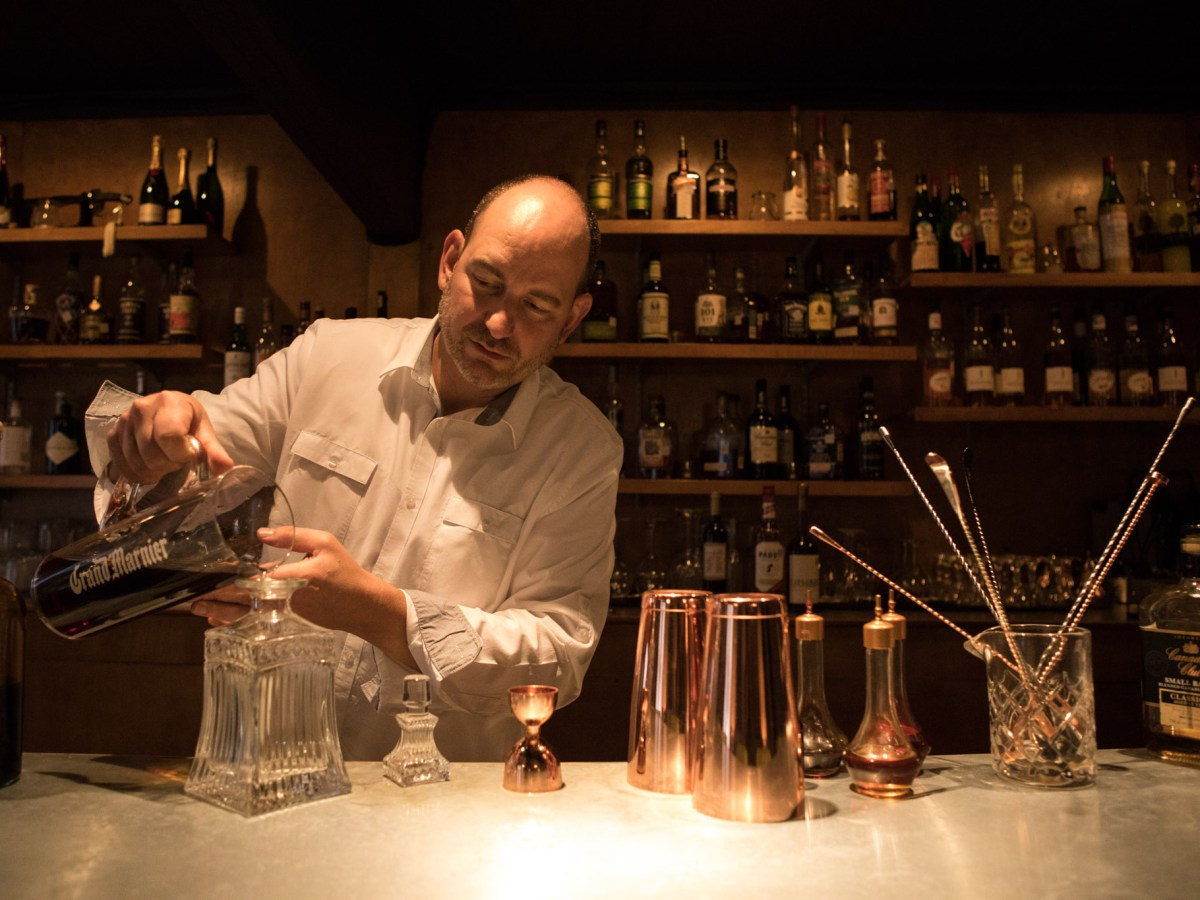 Olaf Harmel prepares a whiskey at The Modernist before opening for the evening.