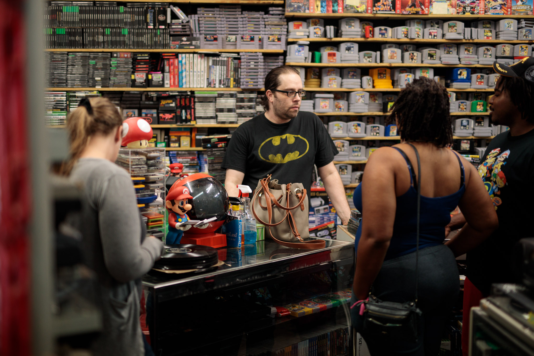 AJ Martinez attends to customers of his video game shop Propaganda Palace, which originally started as his personal collection.