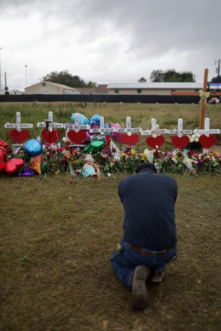 A community member kneels in front of a vigil along Highway 87 for the 26 people that died inside the First Baptist Church of Sutherland Springs.