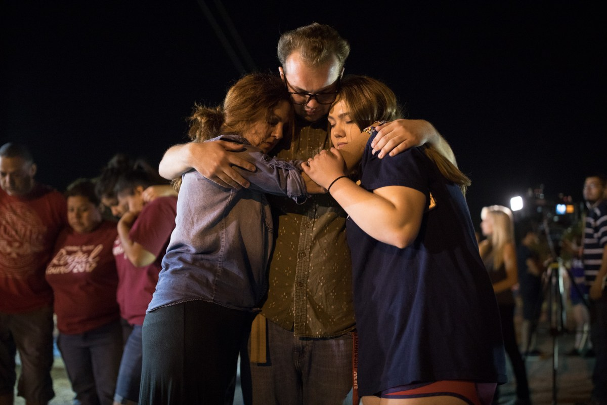 Jennanne Evans, Zane Evans, and Annabel Evans embrace during the vigil in honor of the victims of the church shooting in Sutherland Springs.