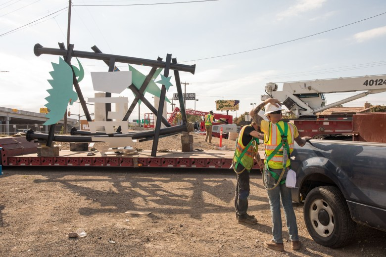 Construction workers prepare to hoist a section of the (i)dream song tower off a truck.