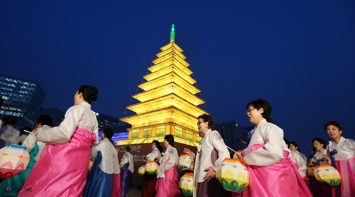 Lotus Lantern Festival celebrants circle an over-sized, pagoda-shaped lantern while carrying their own lotus lanterns in Gwanghwamun, central Seoul on April 16, 2014.