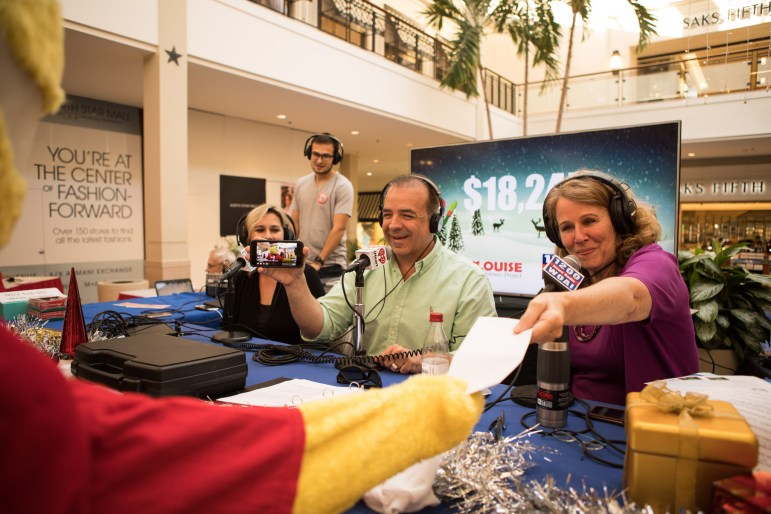 (From left) Radio hosts Cari Laque and Joe Pags record a live stream as Louise Locker, Elf Louise Christmas Project founder, accepts a donation during the WOAI 1200 Elf Louise Radiothon.